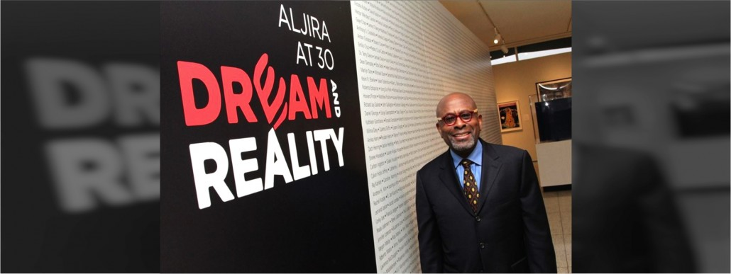 Victor Davson poses in front of an Aljira 30th anniversary banner.